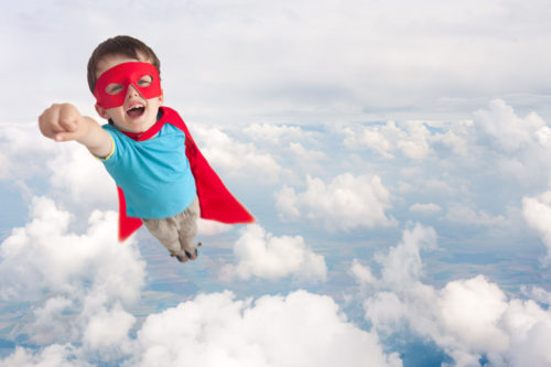 Young child in superman pose flying a level up